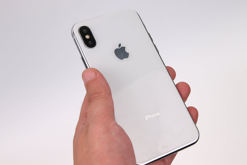 iPhone Xのモックアップを手に持つ