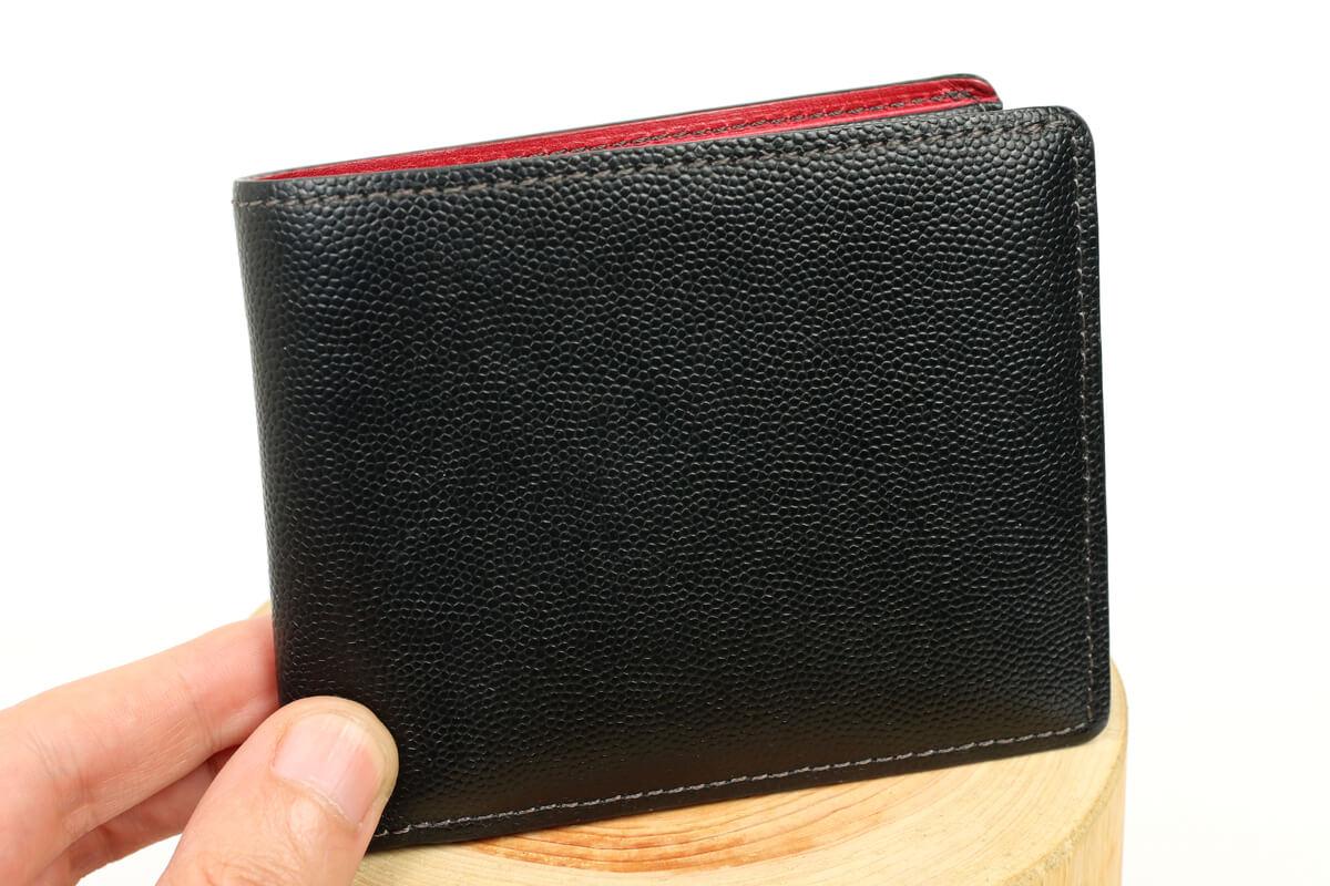 キプリス ペルラネラ 二つ折り財布を指で摘んでいる