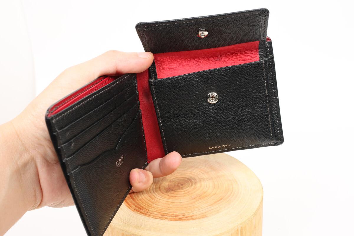 キプリス ペルラネラ 二つ折り財布を手に持つ