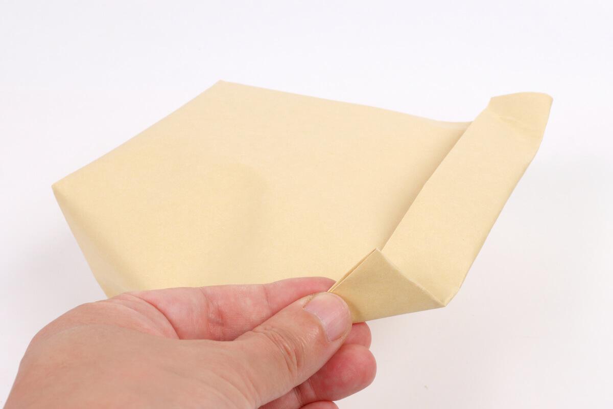 ポップコーンを入れた封筒の耳を折る