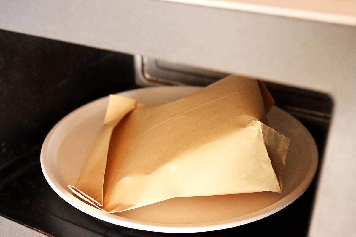 ポップコーンを入れた封筒を電子レンジに入れる