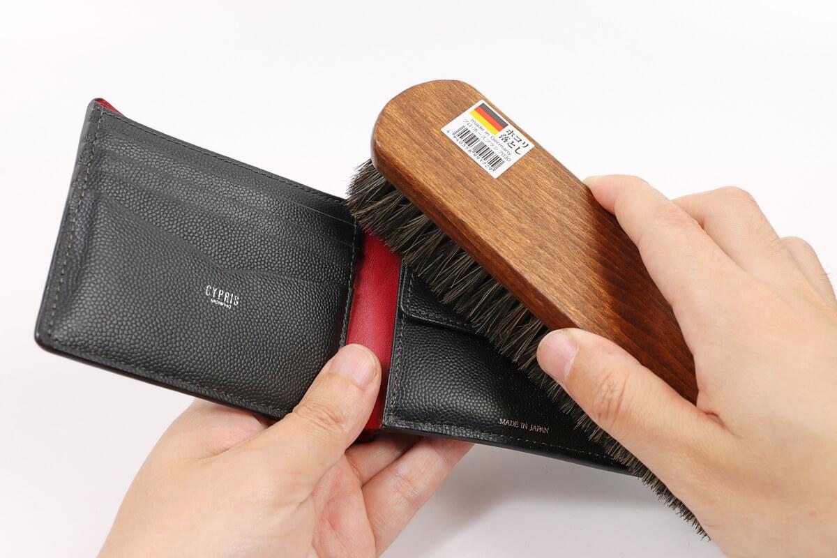 革財布の内側を馬毛ブラシで払う